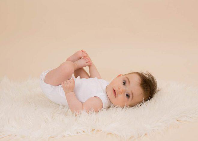 Babyfotos Berlin: Baby mit dunklen Haaren liegt mit dem Rücken auf einem weißen Fell