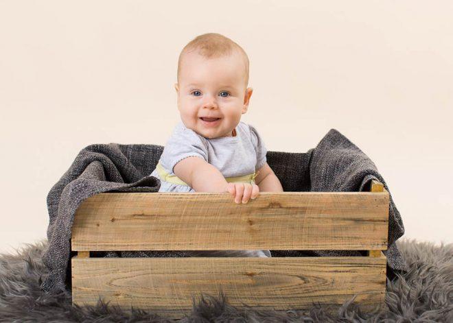 Babyfotos Berlin: Kleines Mädchen sitzt in einer Holzkiste und lacht