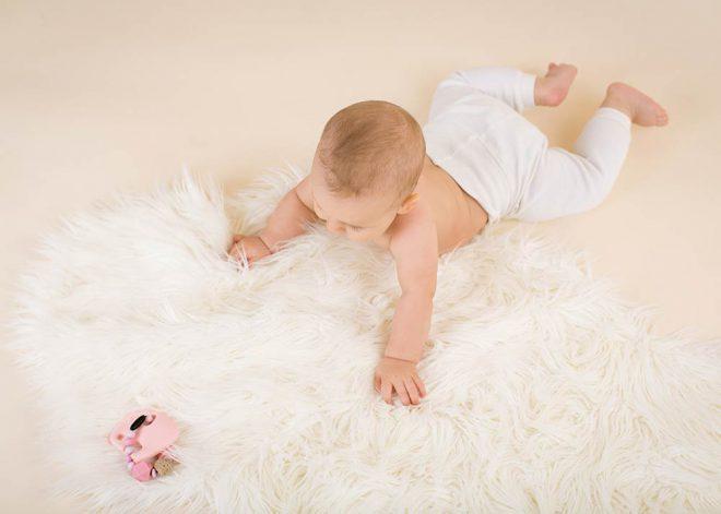 Babyfotos: Baby von oben schaut auf eine Rassel