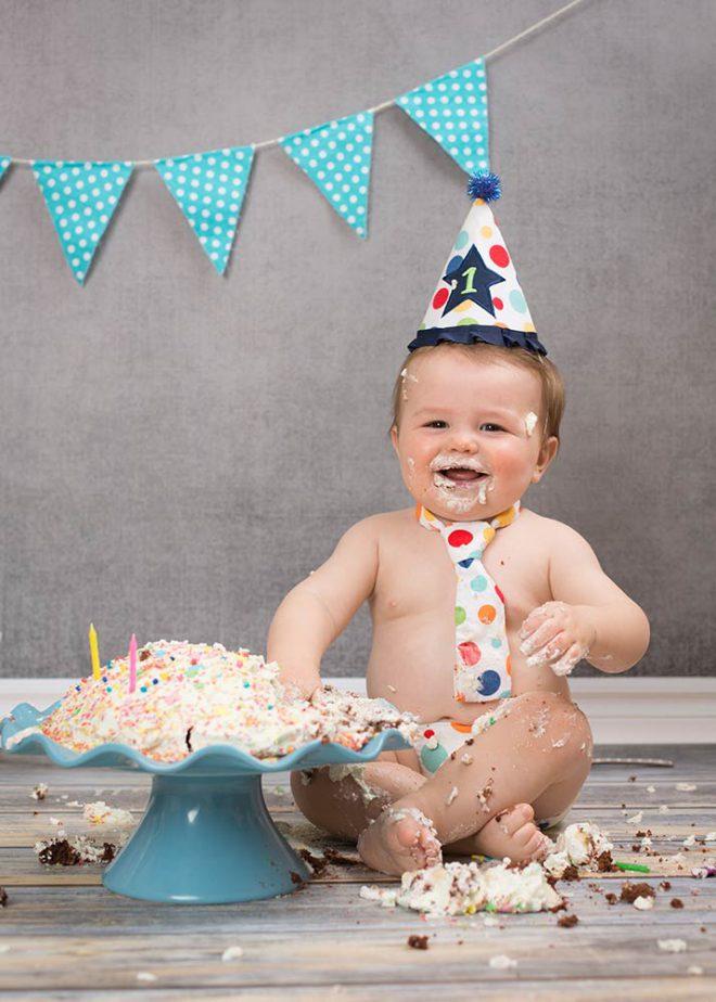Cake Smash Fotos Berlin:Junge mit Partyhut und Krawatte feiert seinen 1. Geburtstag
