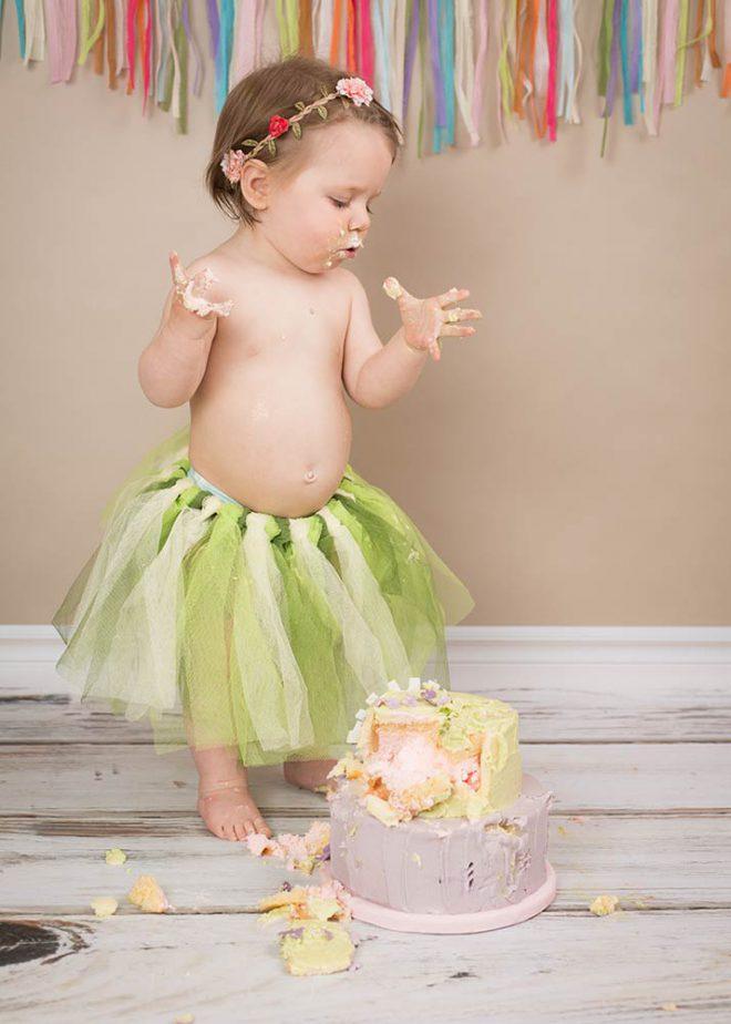 Mädchen mit grünem Tüllrock steht neben ihrer Geburtstagstorte