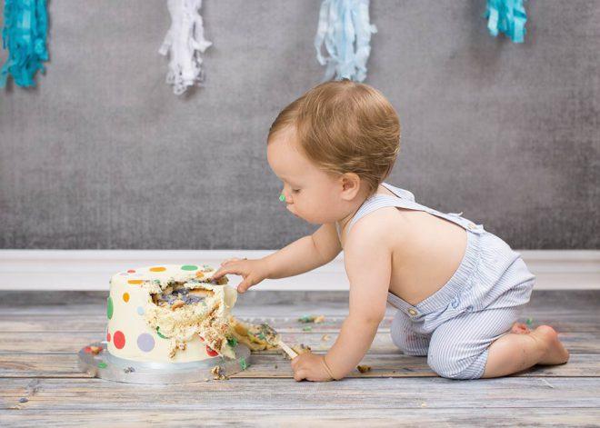 Junge in blauer Latzhose bekommt seine erste Torte geschenkt