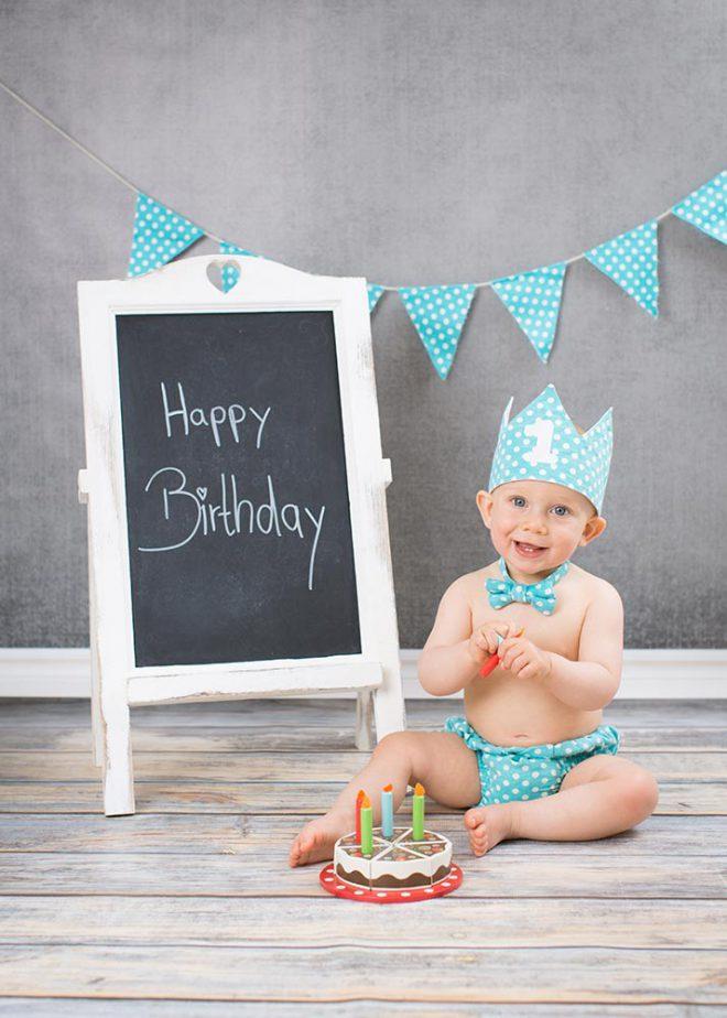 Junge sitzt am ersten Geburtstag in Partyoutfit vor Holzkuchen und Tafel