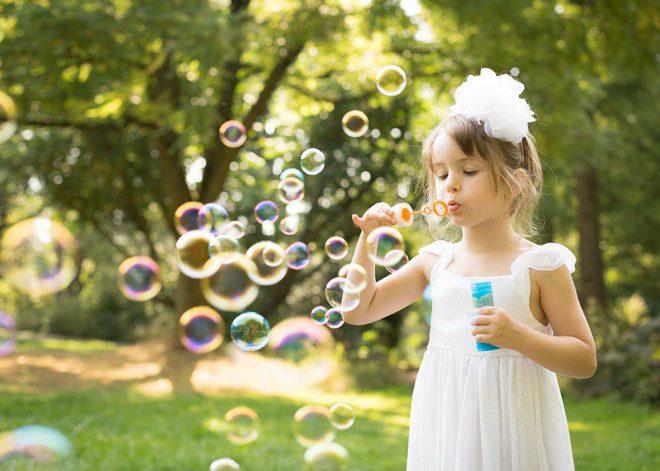 Kinderfotos Berlin: Mädchen in weißem Kleid pustet bunte Seifenblasen