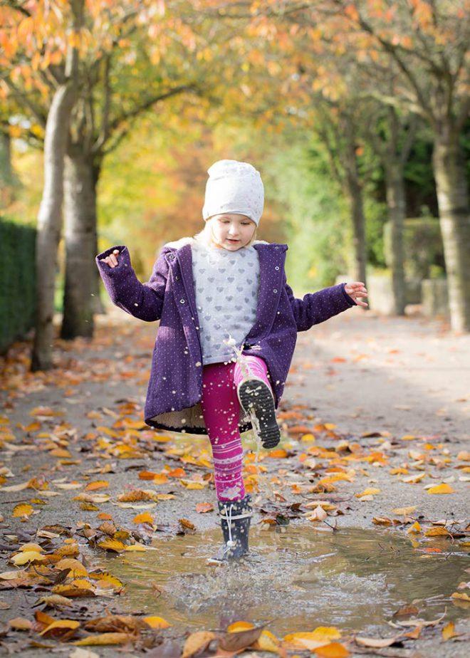 Mädchen spielt im Herbst in einer Regenpfütze mit Gummistiefeln