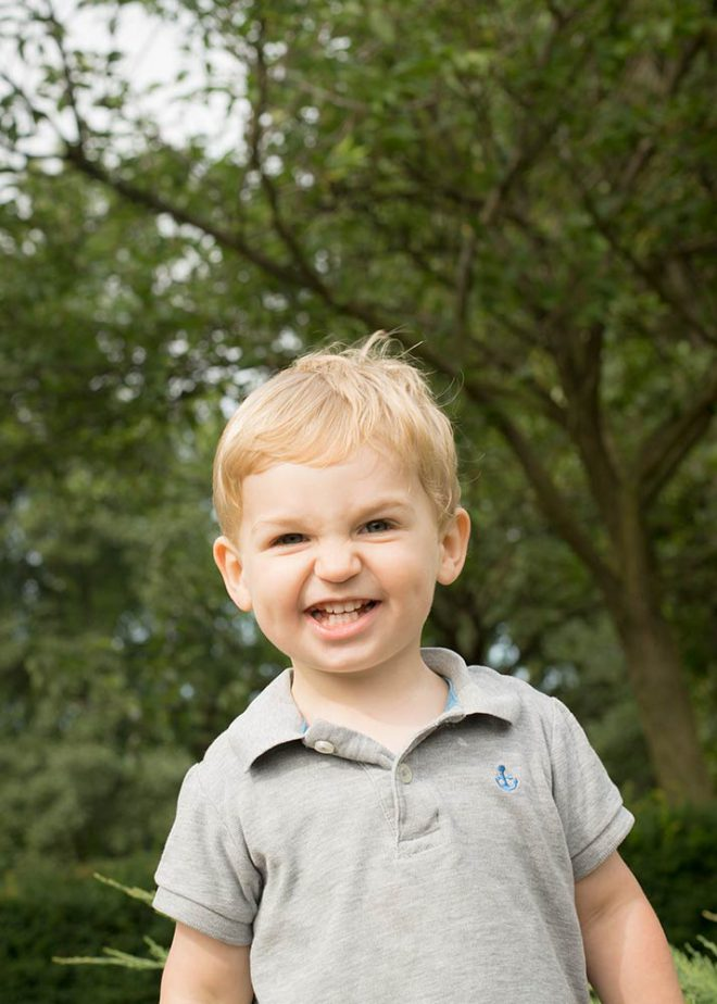 Lachender blonder Junge im Park vor Bäumen