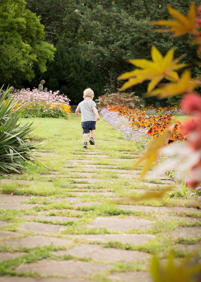 Kleiner blonder Junge läuft über einen Parkweg zwischen blühenden Pflanzen