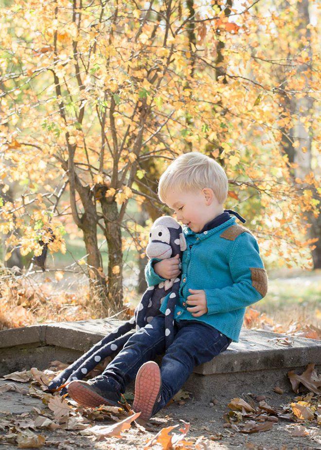 Junge mit blonden Haaren und Stofftier vor Herbstlaub