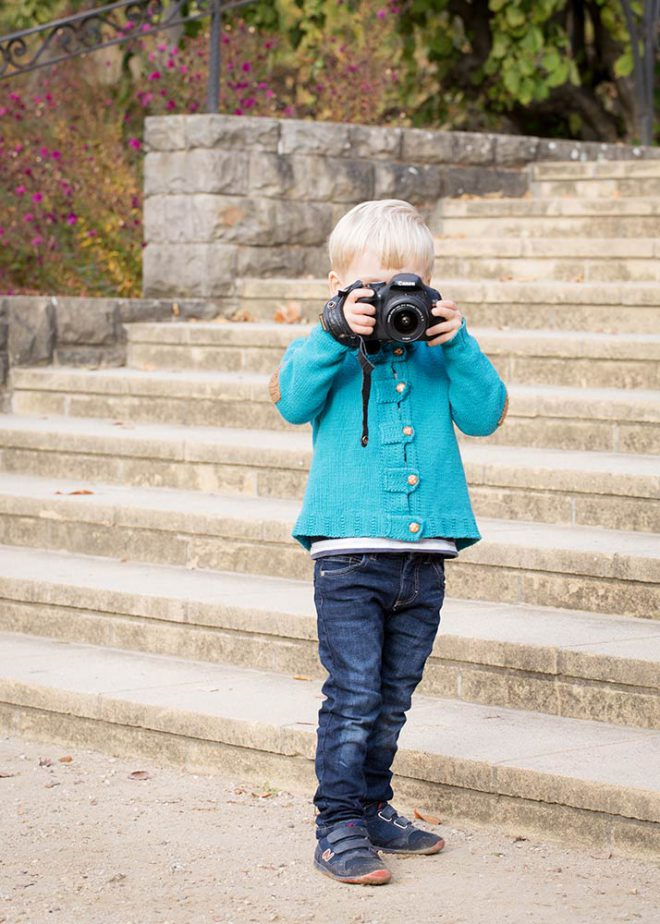 Junge mit blauer Jacke steht mit Kamera vor einer Treppe