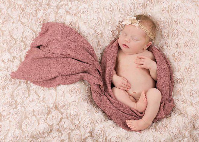 Neugeborenes Mädchen mit Haarband ist in ein Tuch eingewickelt