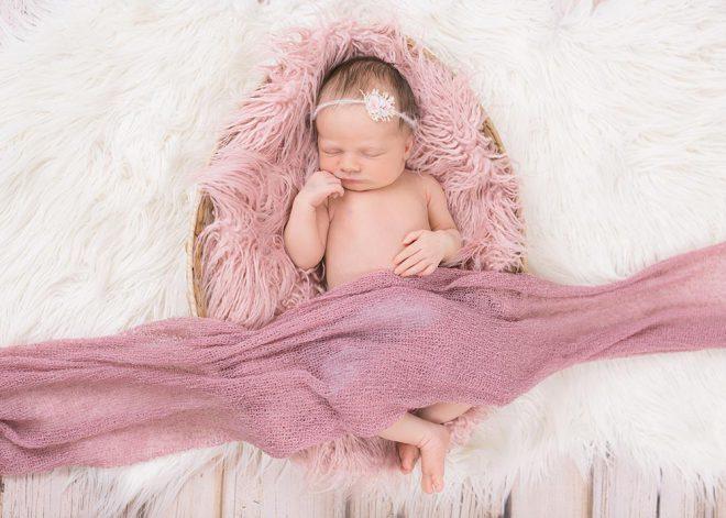 Baby in einem Körbchen mit rosa Fell