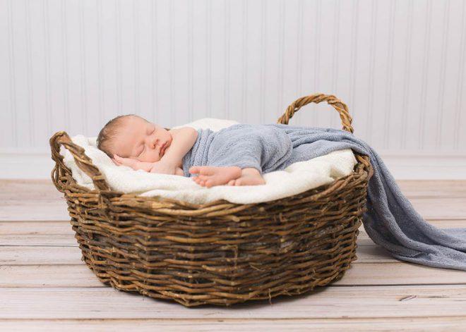 Neugeborenes Baby liegt in blauem Tuch eingewickelt in einem Weidenkorb