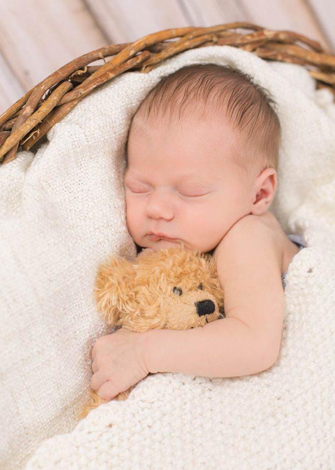 Schlafendes Baby hält Teddy im Arm