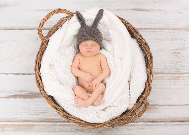 Neugeborenes mit Haeschenmuetze in Korb
