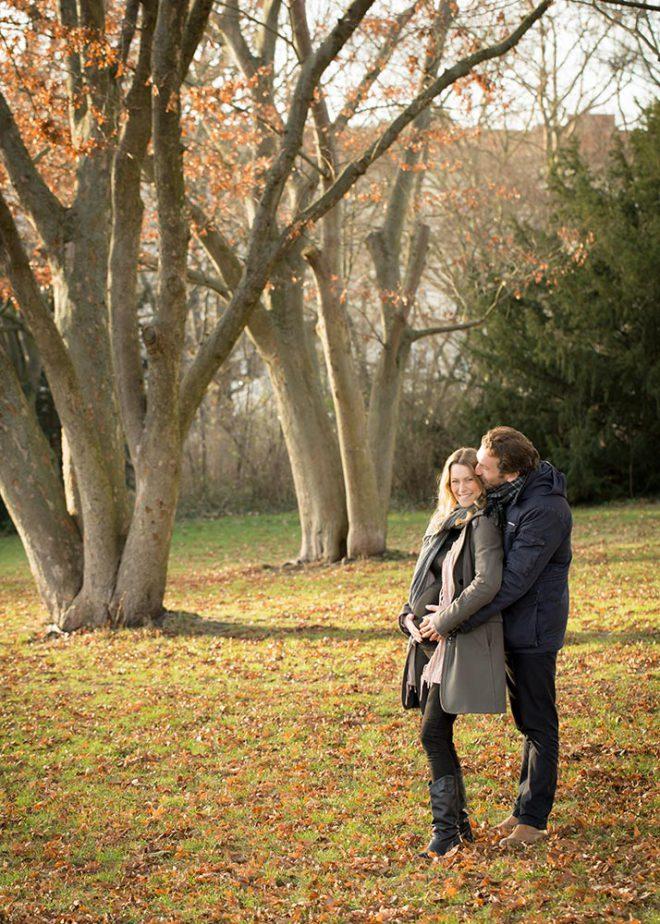 Babybauchfotos Berlin: Schwangeres Paar steht vor Bäumen im Herbst