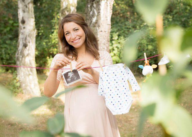 Babybauchfotos Berlin: Schwangere hängt Wäsche auf Leine