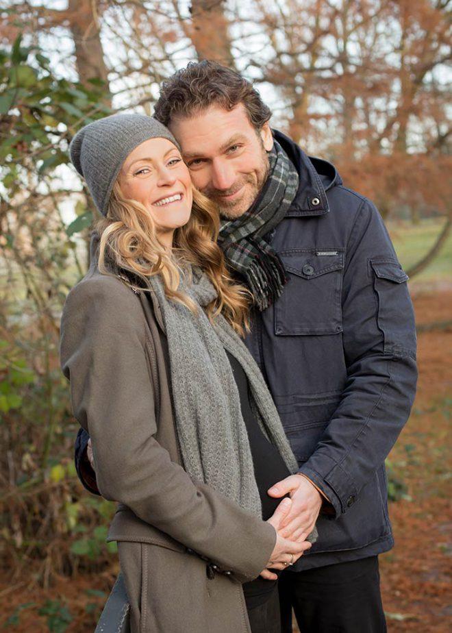 Babybauchfotos: Paar hält den Babybauch und lächelt glücklich