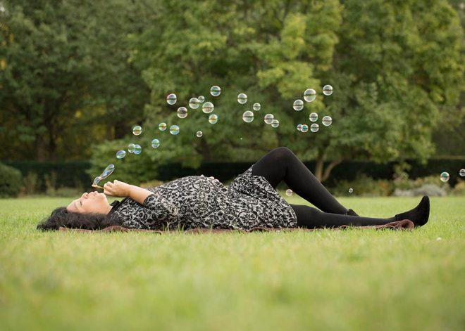 Schwangere liegt auf einer grünen Wiese und pustet Seifenblasen