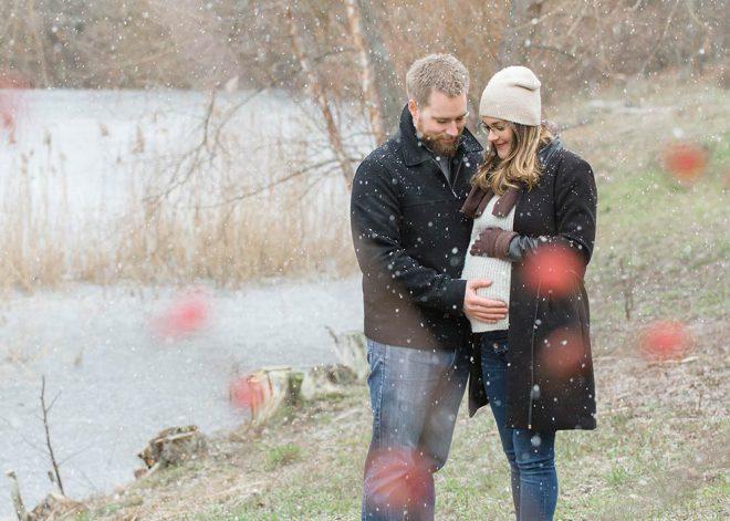 Werdende Eltern stehen im Winter an einem See