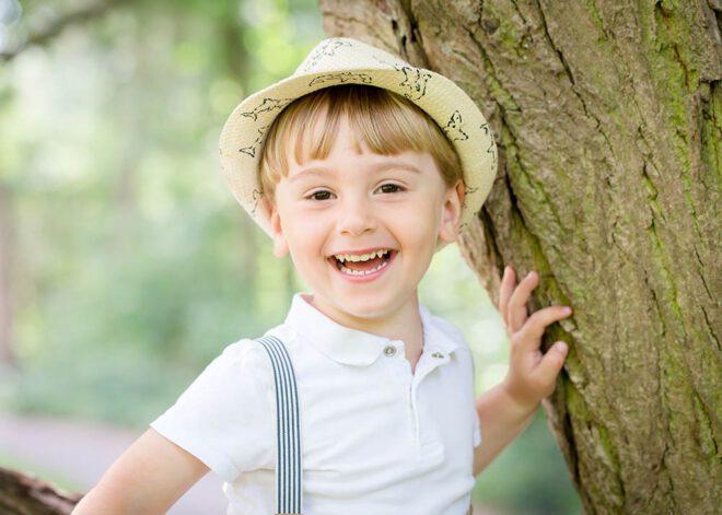 Kinderfotos Berlin: Lachender Junge sitzt auf einem Baum
