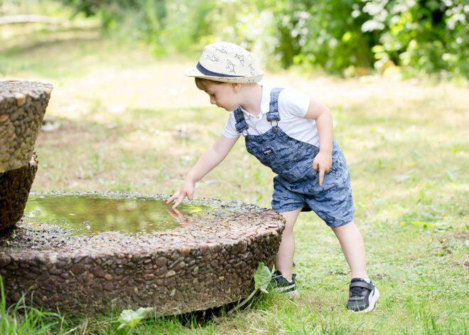 Kinderfotos Berlin: Junge mit Hut spielt an einem Brunnen