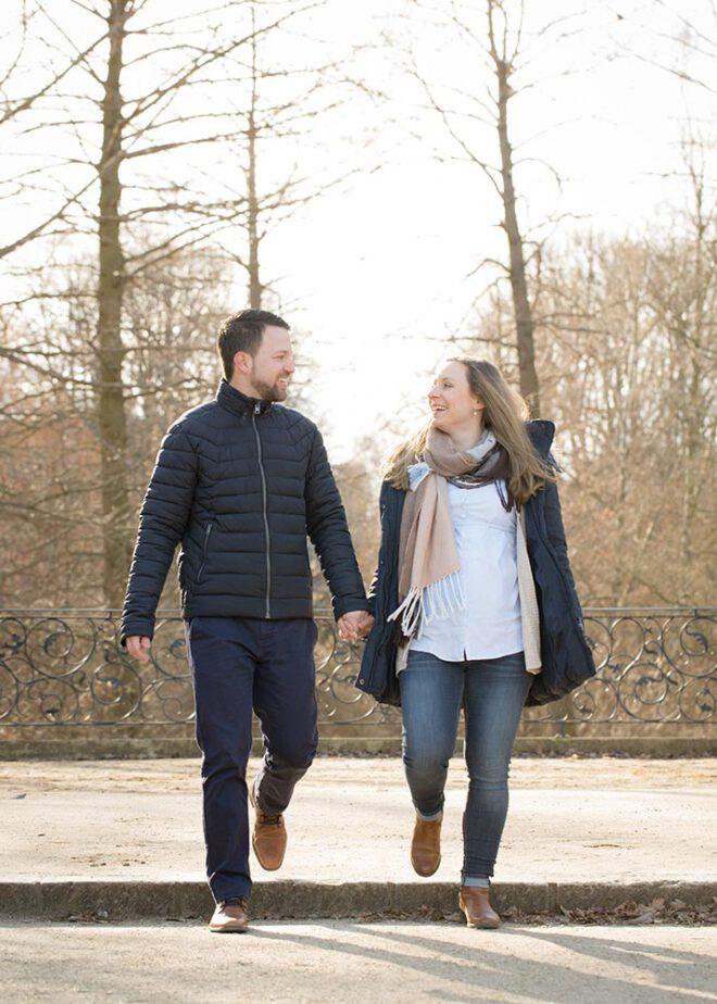Schwangeres Paar spaziert im Winter durch den Park
