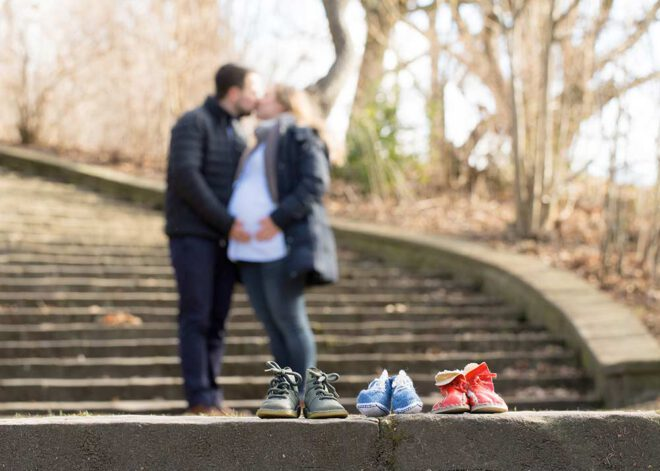 Babybauch Shooting im Winter: Werdende Eltern küssen sich auf einer Treppe