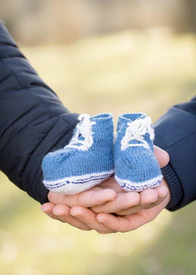 Zwei Hände halten blaue Babyschuhe