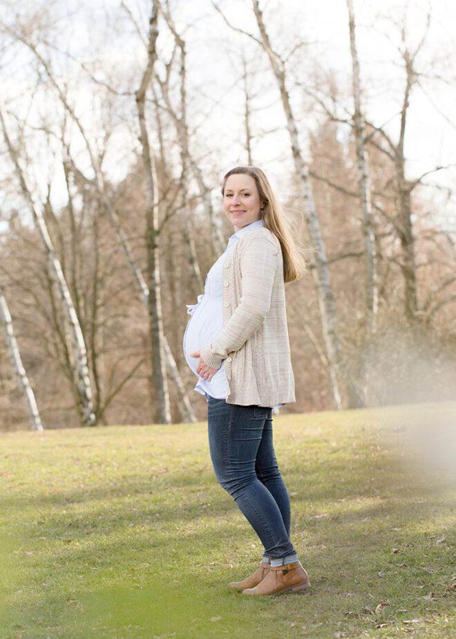 Schwangere Frau steht vor kleinem Birkenwald im Winter