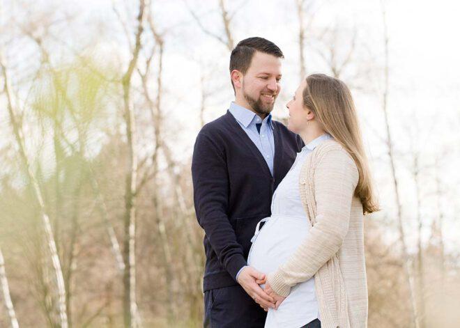 Babybauch Shooting im Winter: Schwangeres Pärchen lächelt sich an
