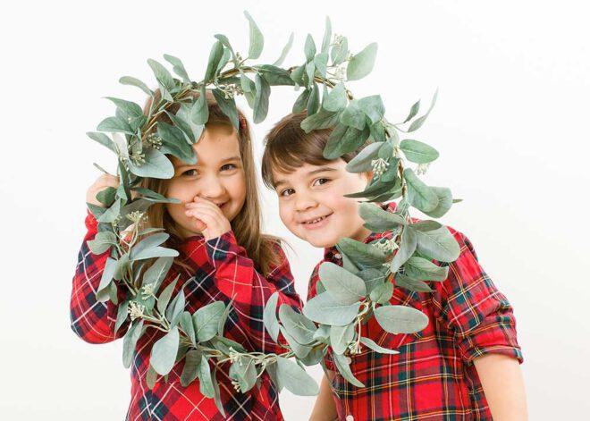 Minimalistische Weihnachtsfotos: Zwillinge mit Eukalyptuskranz