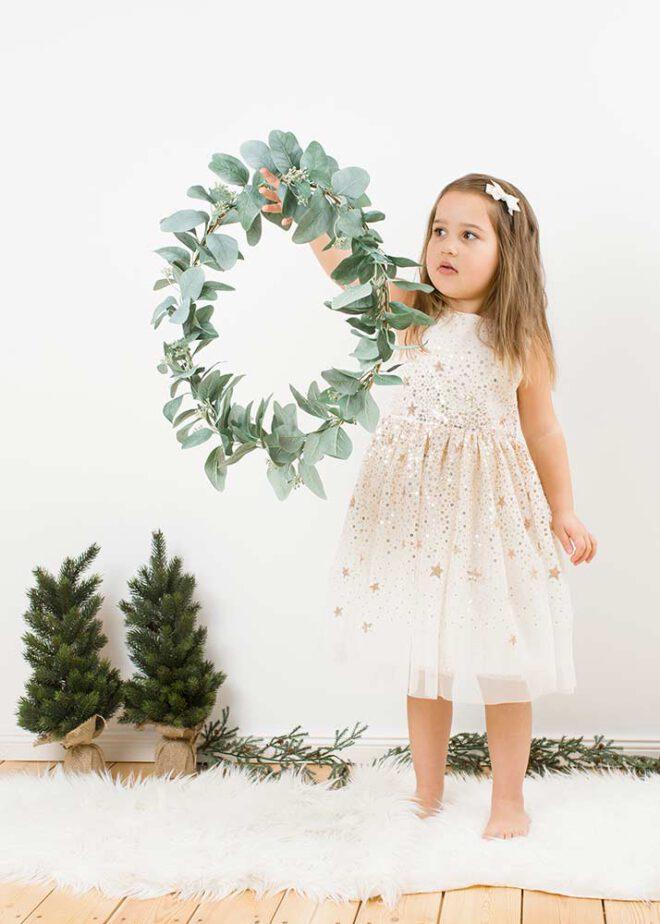 Mädchen hält bei minimalistische Weihnachtsfotos einen Kranz