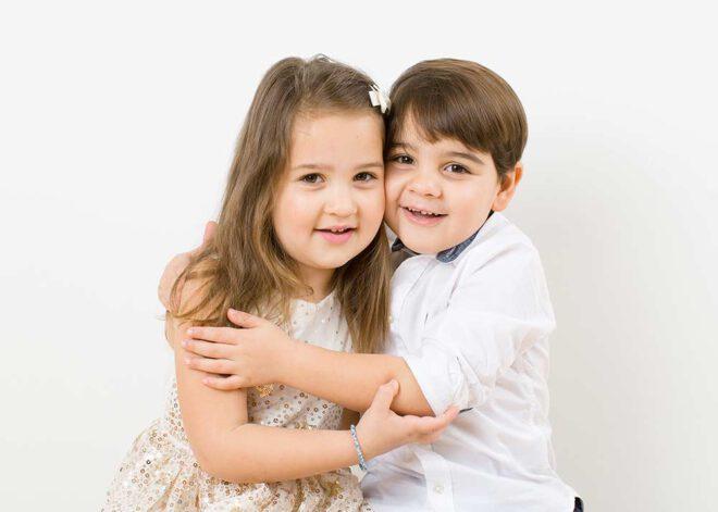 Minimalistische Weihnachtsfotos: Porträt von Zwillingen, die sich umarmen