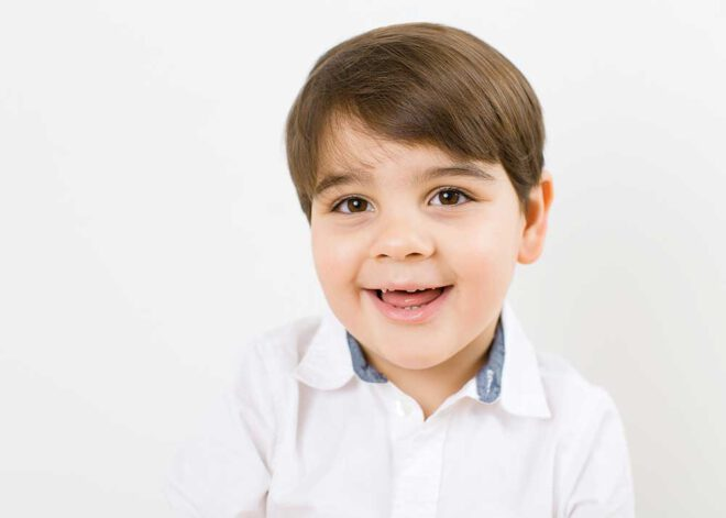 Porträt eines lachenden Jungen im weißen Hemd