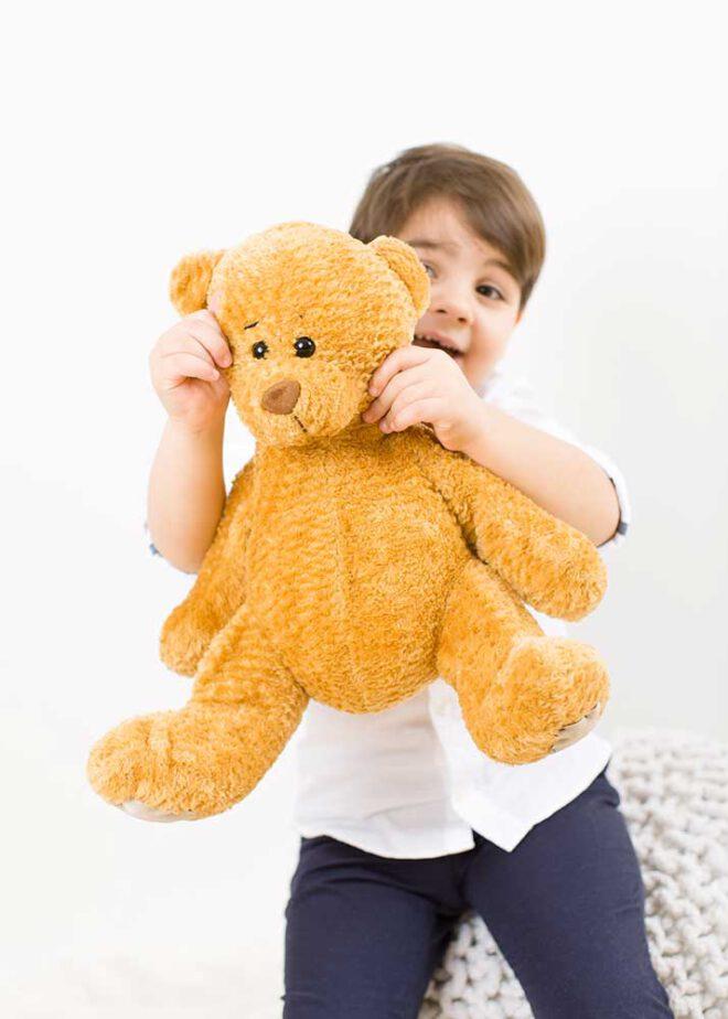 Junge hält Teddybären ind die Kamera