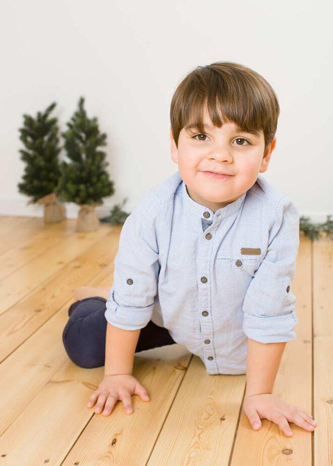 Kleiner Junge in blauem Hemd sitzt auf dem Boden und lächelt in die Kamera