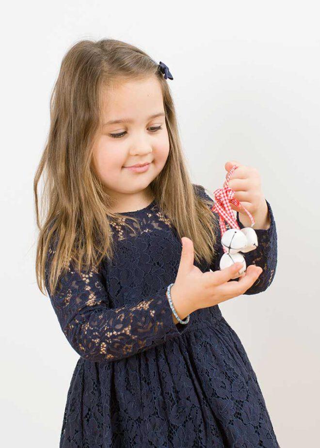 Minimalistische Weihnachtsfotos: Mädchen in blauem Kleid mit Glöckchen in der Hand